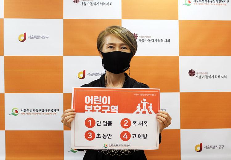 서울중구장애인복지관 정진옥 관장이 어린이 교통안전 릴레이 캠페인에 참여하고 있는 모습입니다.